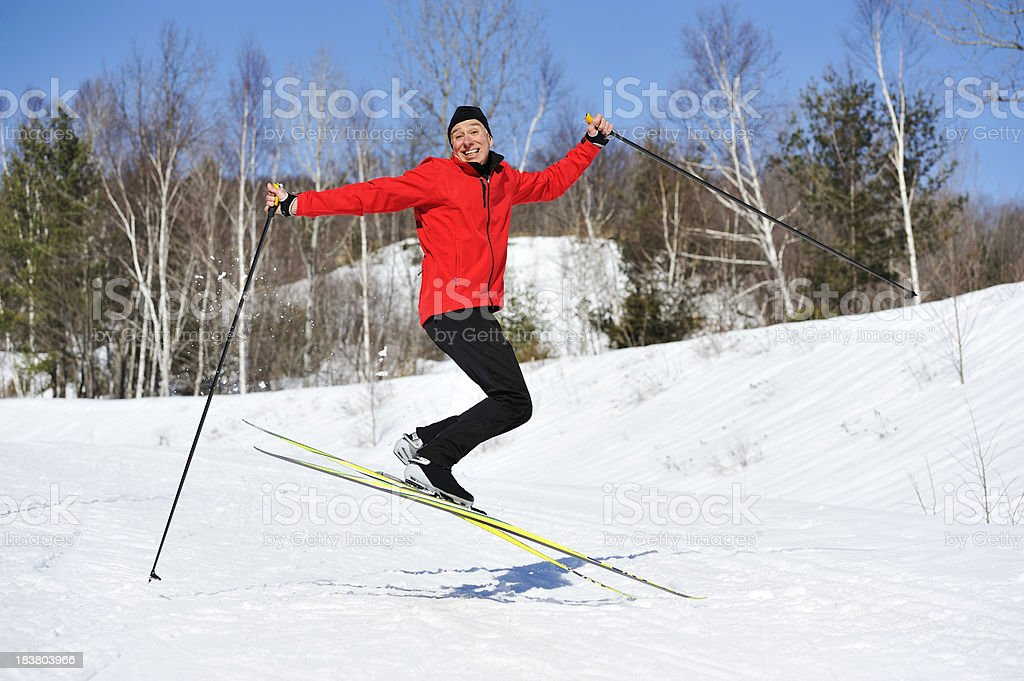 Funny winter scene, man jumping, cross-country skiing stock photo