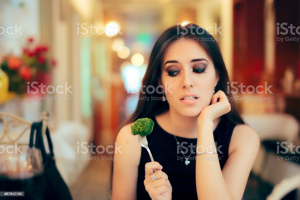 Funny Woman Eating Broccoli At a Party stock photo