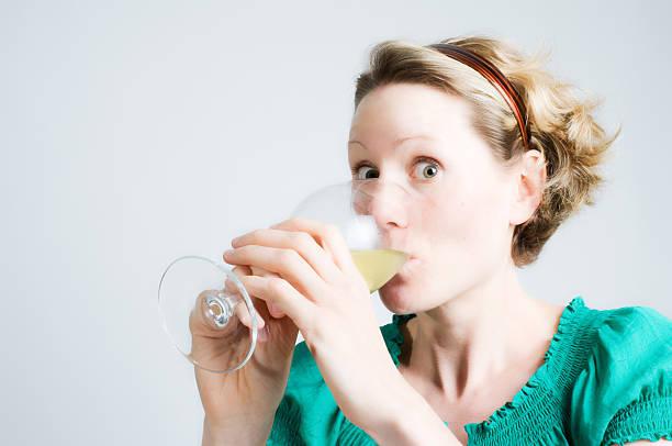 lustige frau guzzling weißwein - lustige trinkspiele stock-fotos und bilder