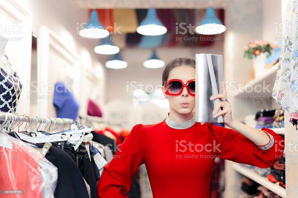 Funny woman in red dress with sunglasses and bag stock photo