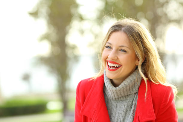 Funny woman laughing in a park in winter stock photo