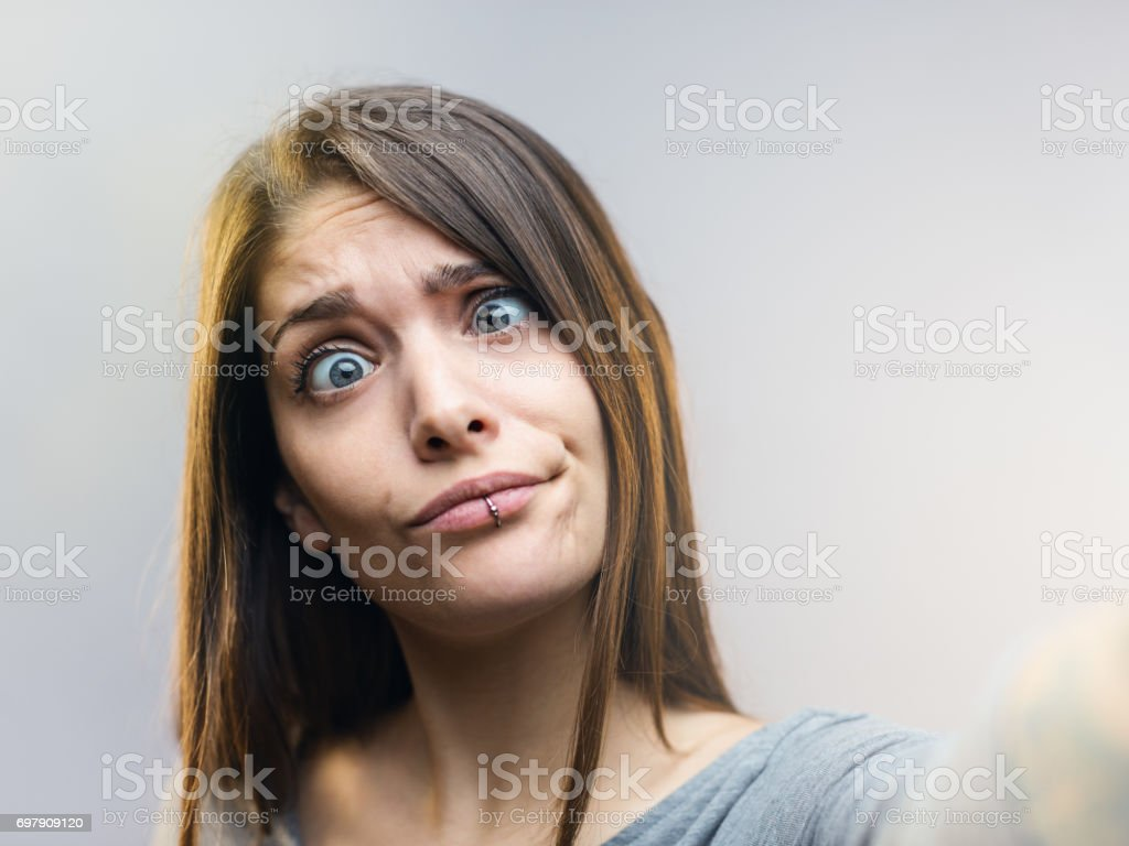 Funny woman posing for a selfie against gray background. stock photo