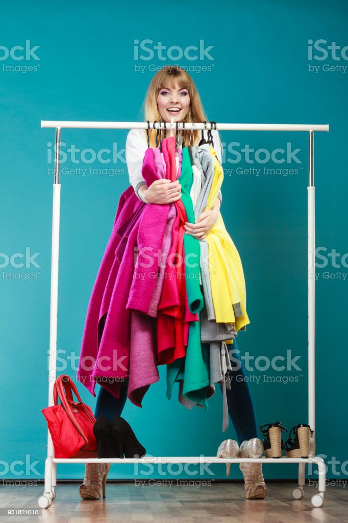 Funny woman taking all clothes in mall or wardrobe stock photo