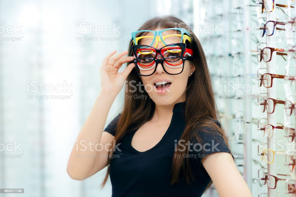 Funny Woman Trying Many Eyeglasses Frames in Optical Store stock photo