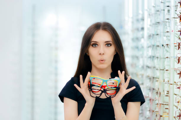 funny woman trying many eyeglasses frames in optical store - sale lenses stock photos and pictures