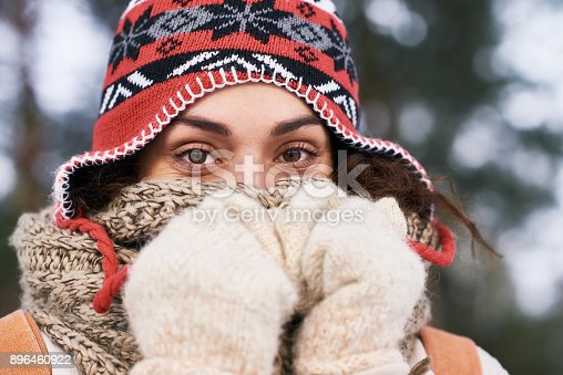 Close-up of beautiful young woman covering nose with wool scarf and mittens looking at camera outdoors