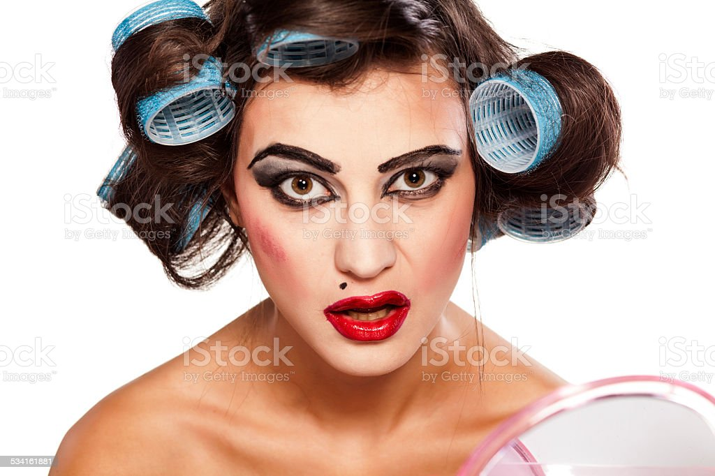 Funny woman with curlers and bad makeup stock photo