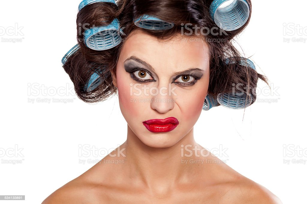 Funny woman with curlers and bad makeup with questionable gesture stock photo