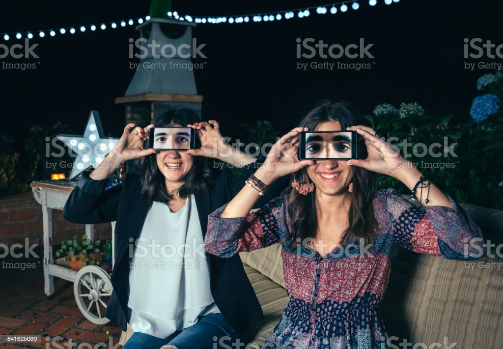 Funny women holding smartphones showing male eyes stock photo