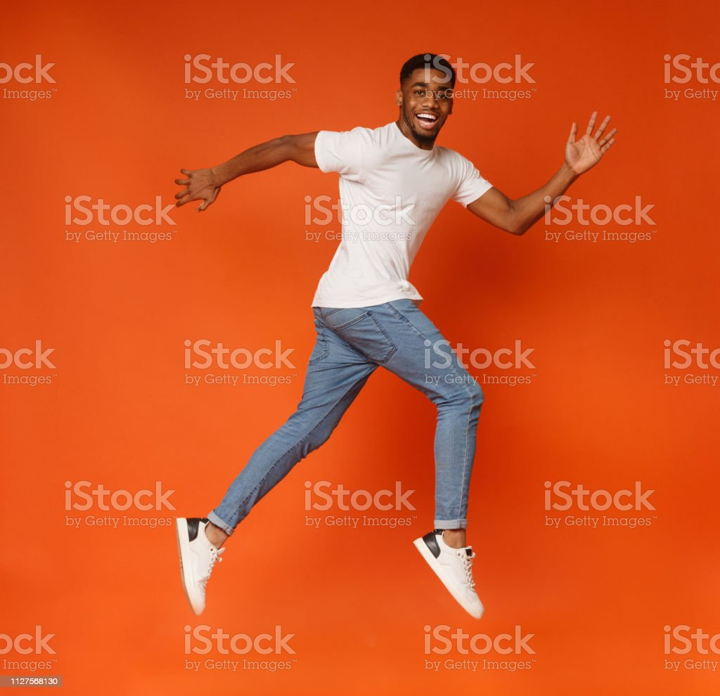 Funny young black man walking on air stock photo