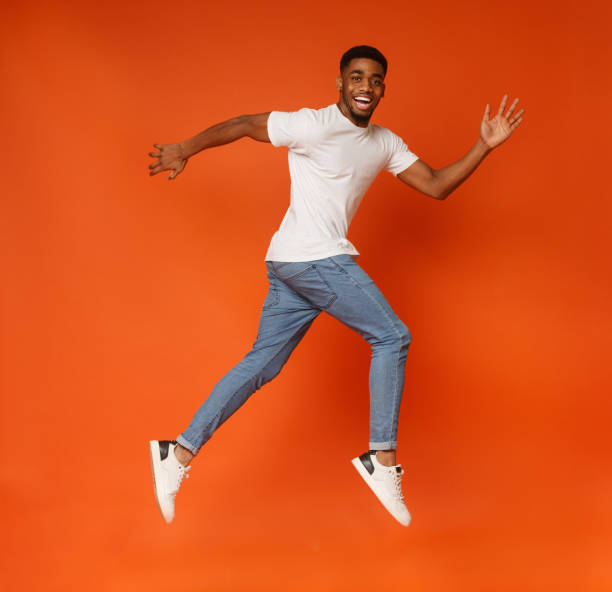 funny young black man walking on air - african youth jumping for joy stock photos and pictures