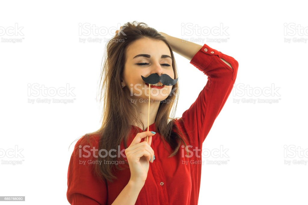 funny young girl in a red blouse stands with closed eyes and keeps paper mustache near the mouth stock photo