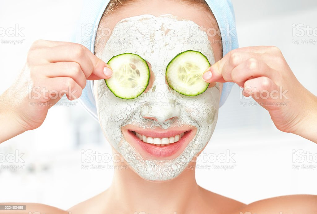 Funny young girl with mask for skin face and cucumbers stock photo