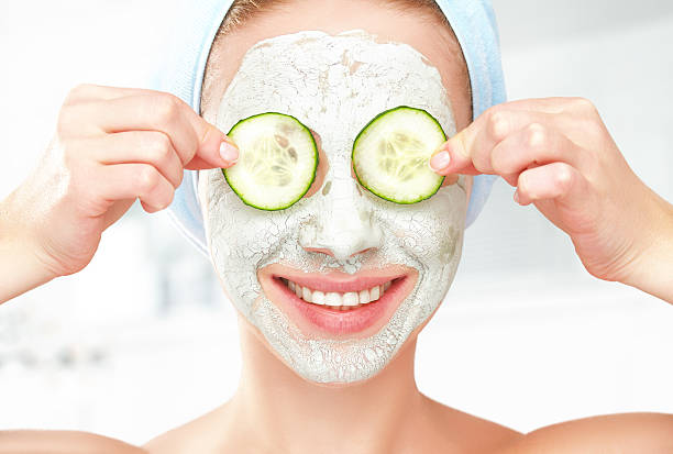 funny young girl with mask for skin face and cucumbers - cucumber stock photos and pictures
