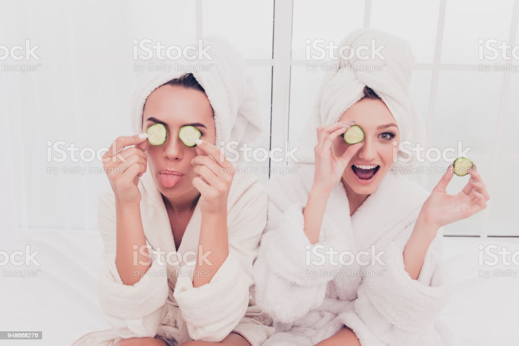 Funny young girls in bathrobes making mask with cucumber and having fun stock photo