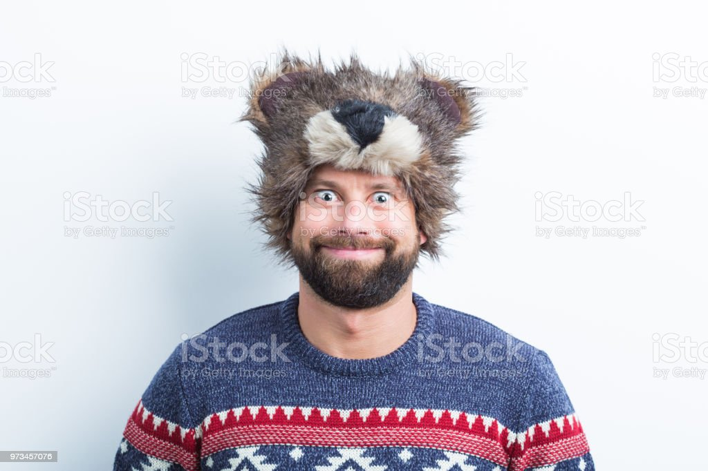 Funny young man in winter wear Portrait of funny young man wearing sweater and winter cap on white background Adult Stock Photo
