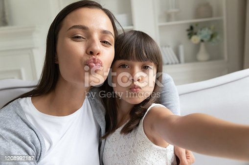 Funny young mom or nanny have fun with little girl posing sending virtual kissed making self-portrait picture together, happy mother enjoy leisure time with small daughter take selfie on gadget