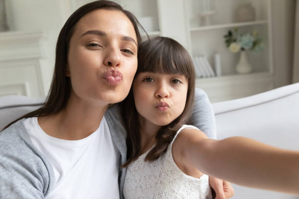 Funny young mom and preschooler daughter make selfie together Funny young mom or nanny have fun with little girl posing sending virtual kissed making self-portrait picture together, happy mother enjoy leisure time with small daughter take selfie on gadget young girls on webcam stock pictures, royalty-free photos & images