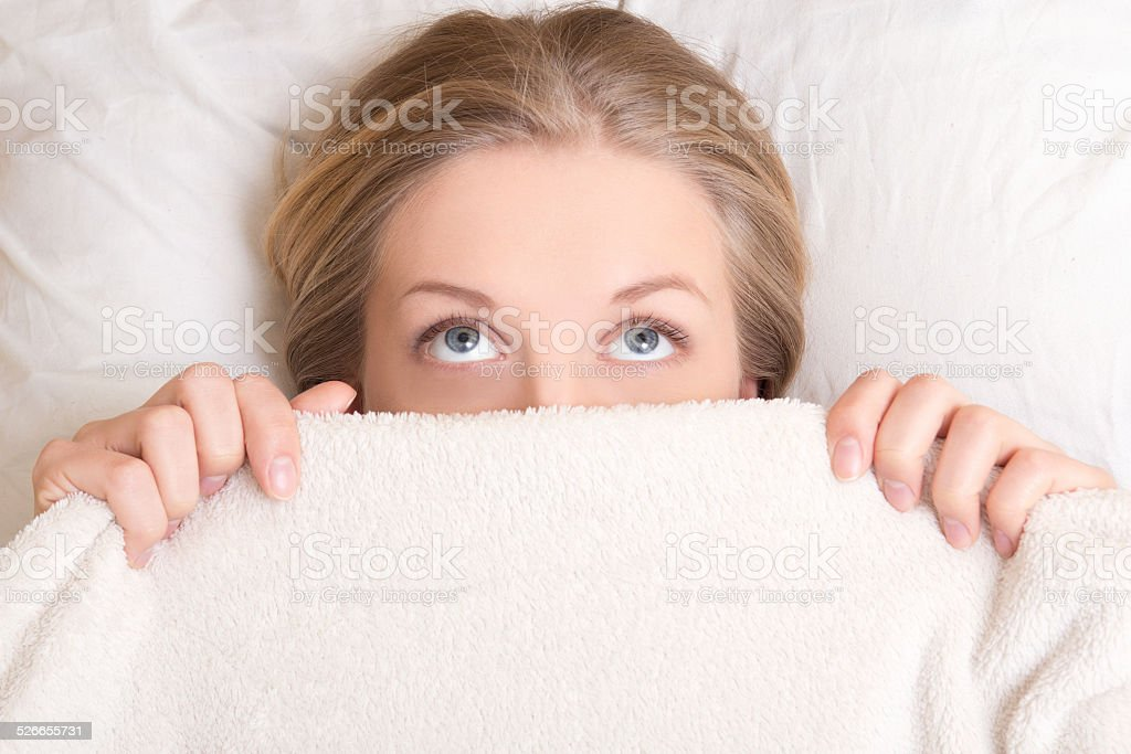funny young woman lying in bed under blanket and dreaming stock photo