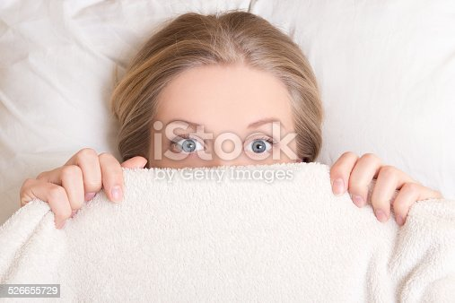 istock funny young woman lying in bed under blanket 526655729