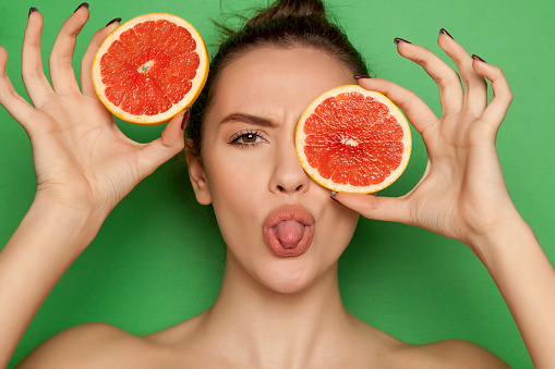 Funny Young Woman Posing With Slices Of Red Grapefruit On Her Face On Green Background Stock Photo & More Pictures of Adult