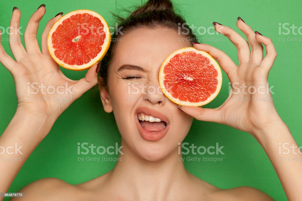 Funny young woman posing with slices of red grapefruit on her face on green background royalty-free stock photo