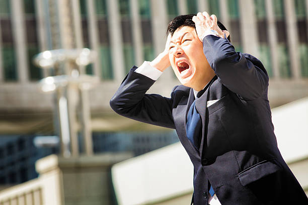 Furious angry Japanese office worker screams in despair stock photo