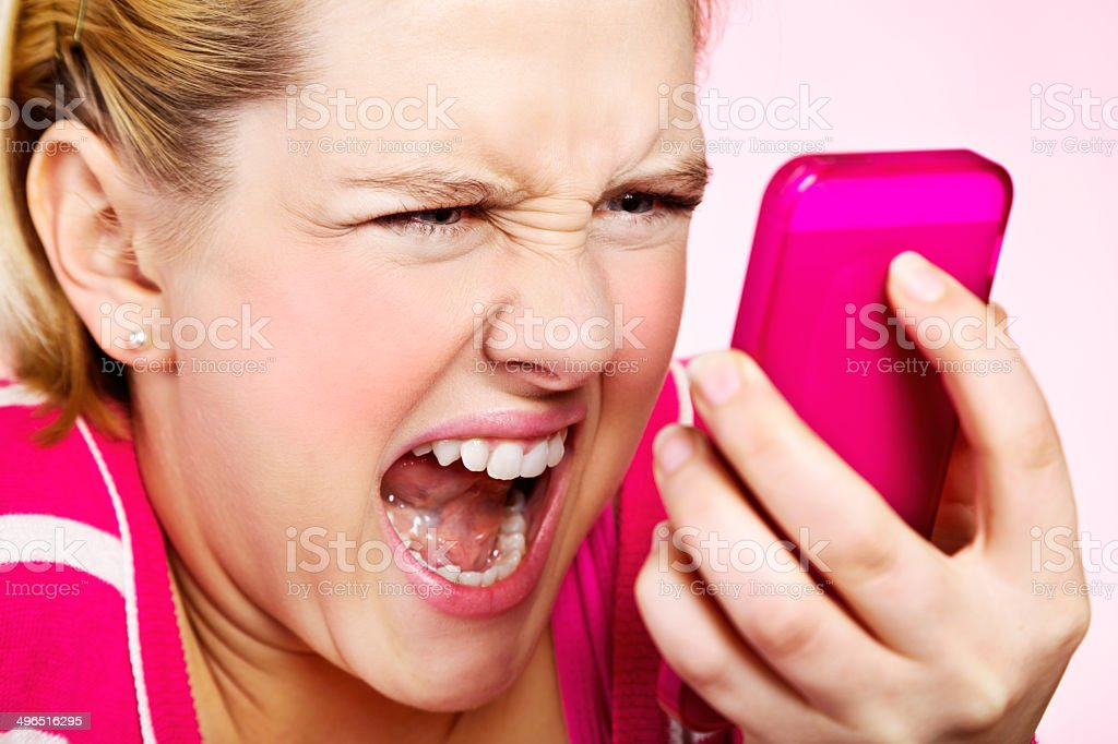 Furious blonde teenager yells angrily at her phone stock photo