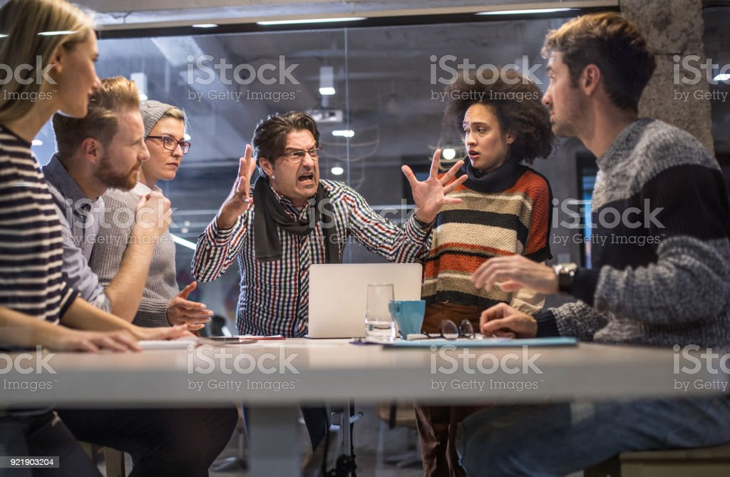Furious boss shouting at his team on a meeting in the office. Angry manager shouting at his coworkers during a meeting in the office. Adult Stock Photo