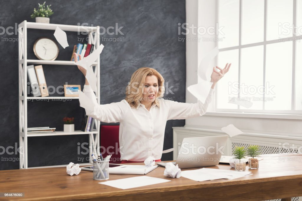 Furious business woman throwing working documents at office desktop royalty-free stock photo