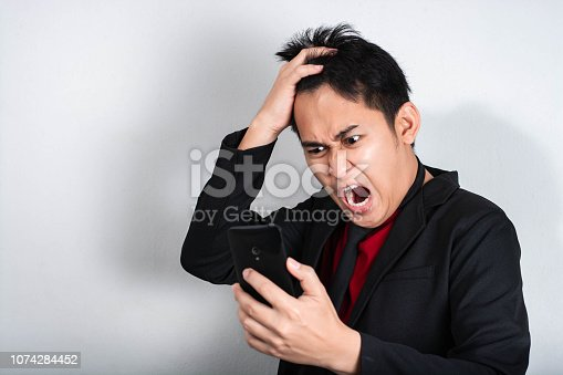 Furious businessman outraged on the phone in his office,Businessman furiously,Businessman  Asia.