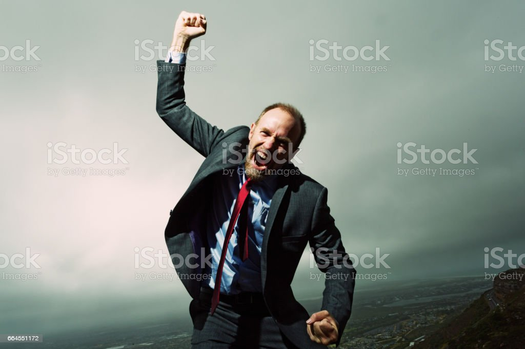 Furious businessman rages at fate against a stormy sky stock photo