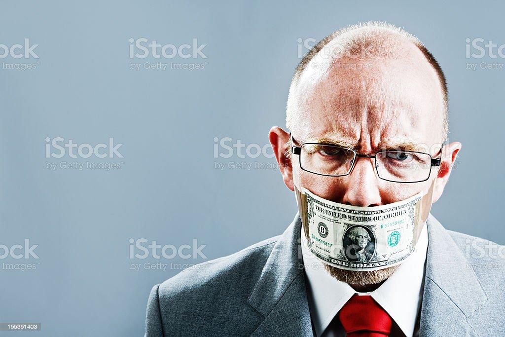 Furious businessman silenced and censored by dollar bill gag stock photo