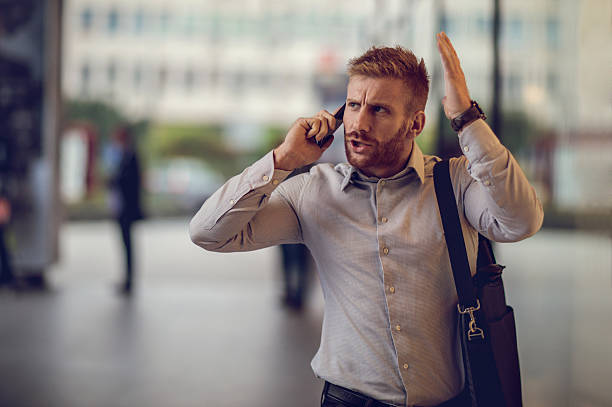 Furious businessman talking to someone over smart phone. stock photo