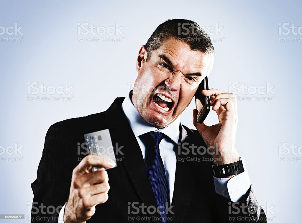 Furious businessman with credit card and phone: maxed out maybe? stock photo