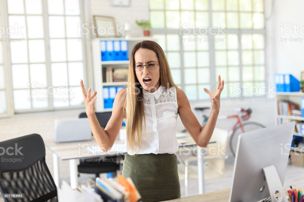 Furious businesswoman shouting at work stock photo