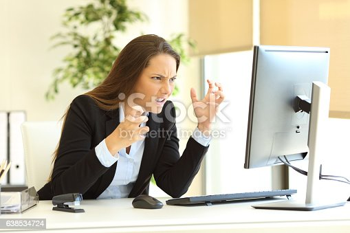593328060istockphoto Furious businesswoman using a computer 638534724
