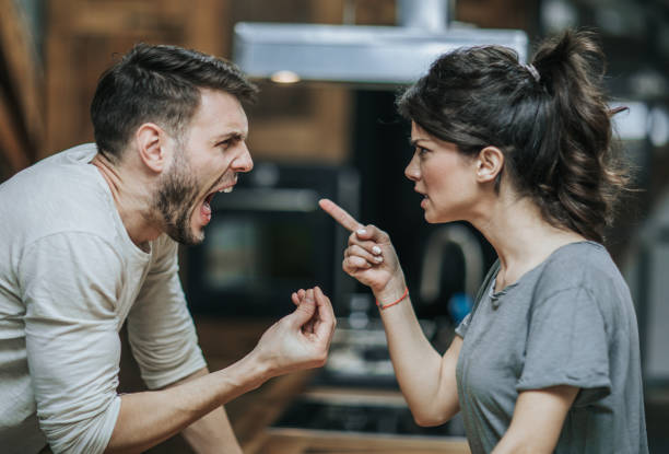 Furious couple arguing while having problems in their relationship. Aggressive couple arguing about their problems at home. agitation stock pictures, royalty-free photos & images