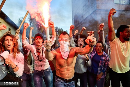 Angry crowd of people with lit torch on public demonstrations.