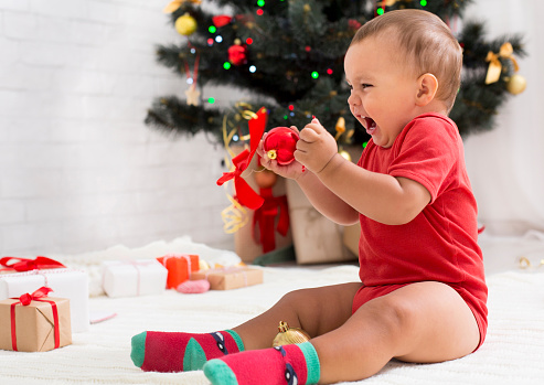 Furious emotional baby yelling, sitting with decorations near Christmas tree