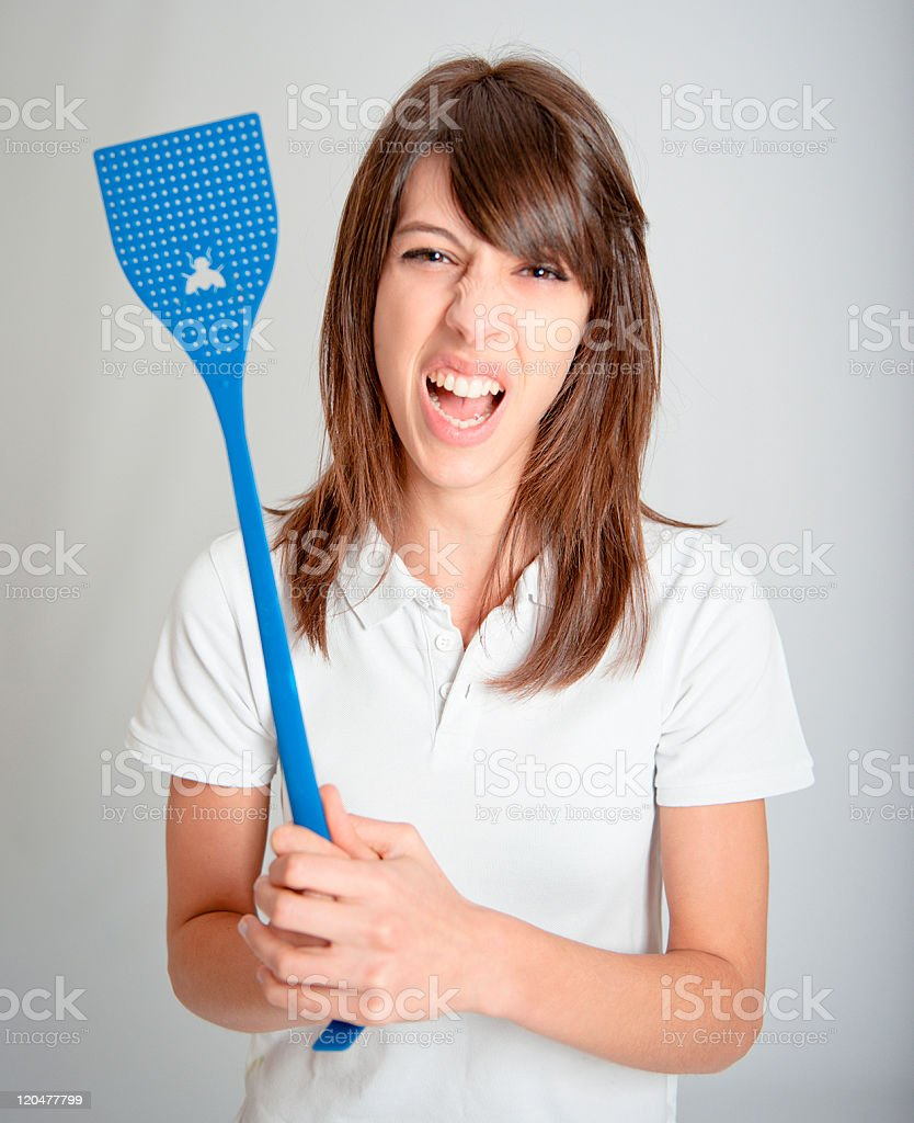 Furious girl with flyswatter stock photo