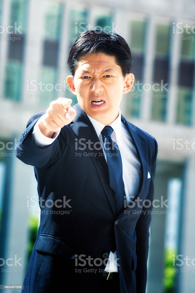 Furious Japanese businessman points and threatens stock photo