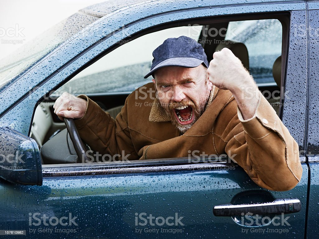Furious male driver shakes his fist out of car window stock photo
