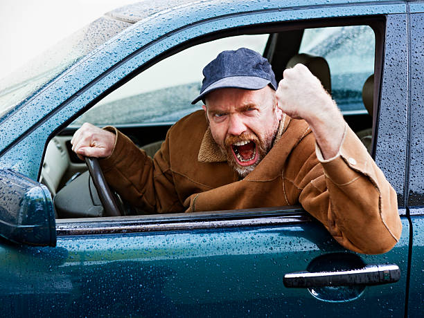 furious male driver shakes his fist out of car window - swearing stockfoto's en -beelden
