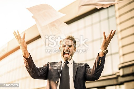 Angry and frustrated mature businessman shouting and getting rid of all the bills and documents in front of office building.