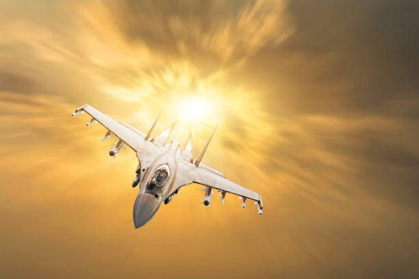 Furious military fighter jet with fire from engines flies in the orange sunset sky. Furious military fighter jet with fire from engines flies in the orange sunset sky fighter plane stock pictures, royalty-free photos & images