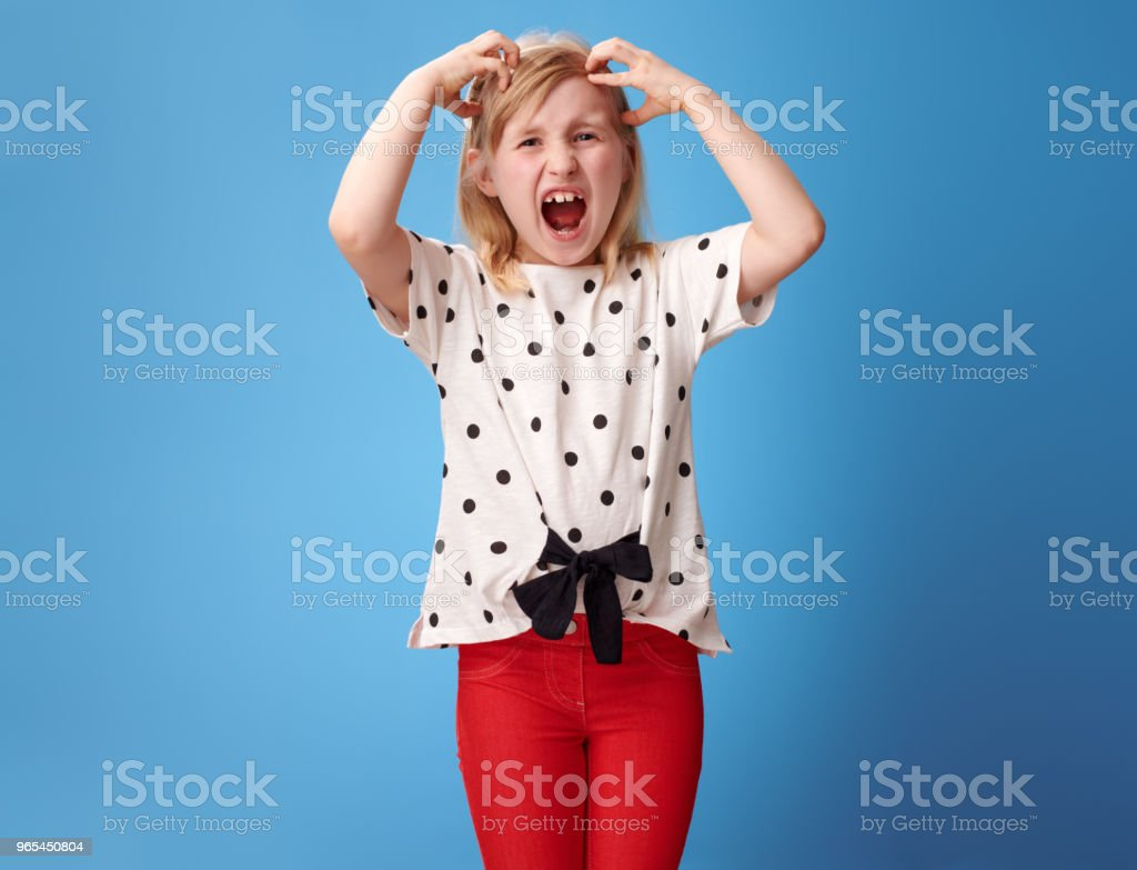 furious modern child in red pants on blue scratching head royalty-free stock photo