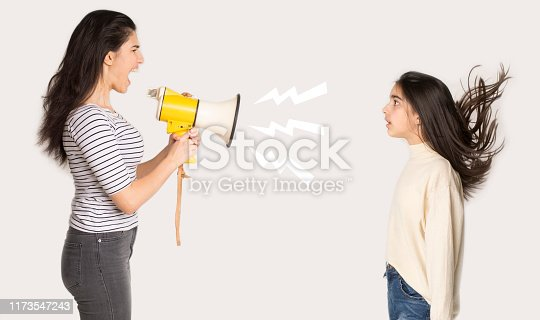 Furious mother shouting at girl through loudspeaker over light background, side view