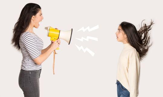 istock Furious mother shouting at girl through loudspeaker 1173547243