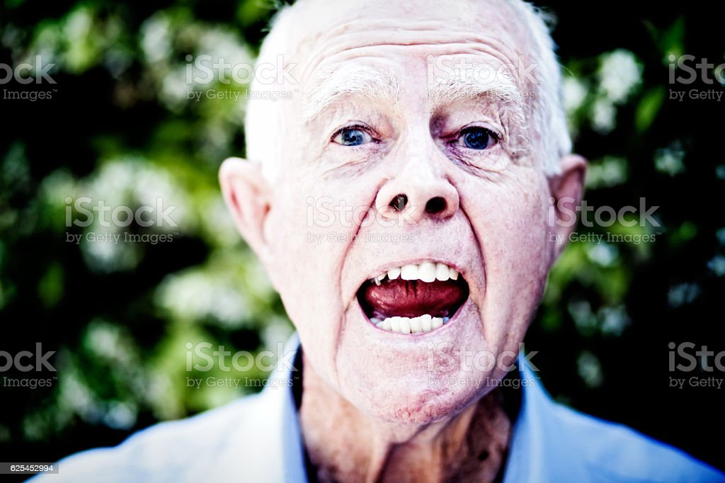 Furious old man shouts angrily, senile or simply enraged stock photo
